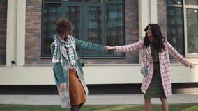 Duas jovens mulheres atrativas estão tendo o divertimento, estão enganando-o ao redor e estão dançando-o na rua As amigas passam  vídeos de arquivo
