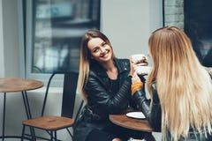 Duas jovens mulheres bonitas na roupa da forma que tem o resto que falam e café bebendo no restaurante exterior Foto de Stock Royalty Free