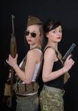 Duas jovens mulheres bonitas no uniforme militar com armas Fotografia de Stock