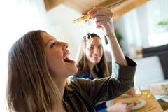 Duas jovens mulheres bonitas que comem o alimento japonês em casa imagem de stock