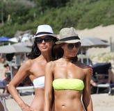Duas jovens mulheres bonitas que dão uma volta em uma praia Amigos fêmeas que andam na praia e que riem em um dia de verão Fotos de Stock Royalty Free