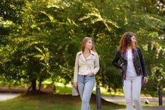 Duas jovens mulheres bonitas que falam ao andar em Sunny Park Uma comunicação e bisbolhetice fotografia de stock royalty free