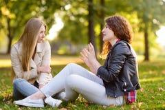 Duas jovens mulheres bonitas que falam ao sentar-se na terra no parque ensolarado girlfriends imagem de stock royalty free