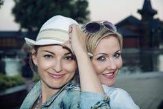 Duas jovens mulheres bonitas que levantam na frente da câmera Foto de Stock