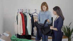 Duas jovens mulheres bonitas são contratadas na análise do vestuário As amigas escolhem equipamentos e pegaram imagens vídeos de arquivo