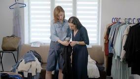 Duas jovens mulheres bonitas são contratadas na análise do vestuário As amigas escolhem equipamentos e pegaram imagens filme