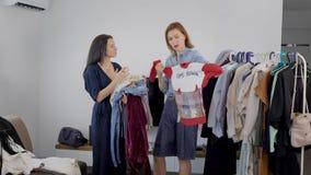 Duas jovens mulheres bonitas são contratadas na análise do vestuário As amigas escolhem equipamentos e pegaram imagens video estoque