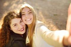 Duas jovens mulheres bonitas tomam o selfie no parque ensolarado girlfriends imagens de stock