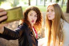 Duas jovens mulheres bonitas tomam o selfie no parque ensolarado girlfriends fotografia de stock royalty free