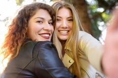 Duas jovens mulheres bonitas tomam o selfie no parque ensolarado girlfriends fotografia de stock