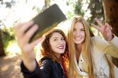 Duas jovens mulheres bonitas tomam o selfie no parque ensolarado girlfriends imagens de stock royalty free