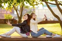 Duas jovens mulheres bonitas tomam selfies em um parque ensolarado ao mesmo tempo girlfriends foto de stock royalty free