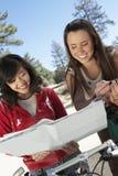 Duas jovens mulheres com Mountain bike que leem o mapa Foto de Stock Royalty Free