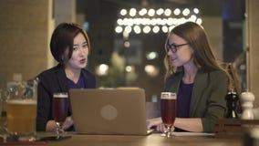 Duas jovens mulheres com portátil que falam no café do ar livre na noite filme