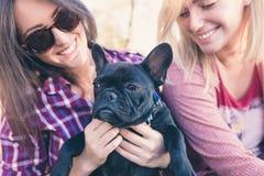 Duas jovens mulheres com seu cão pequeno bonito imagens de stock royalty free
