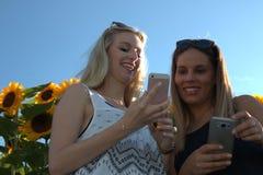 Duas jovens mulheres com telefone esperto fora fotografia de stock royalty free