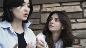Duas jovens mulheres com um portátil que trabalha fora filme