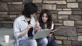 Duas jovens mulheres com um portátil que trabalha fora video estoque