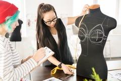 Duas jovens mulheres criativas que trabalham na oficina Imagens de Stock
