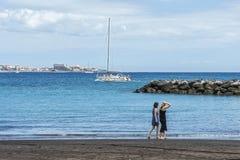Duas jovens mulheres dão uma volta ao longo da praia perto da água Imagem de Stock