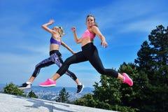 Duas jovens mulheres da felicidade que saltam sobre o céu azul fotos de stock