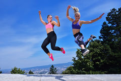 Duas jovens mulheres da felicidade que saltam sobre o céu azul imagem de stock royalty free