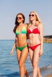 Duas jovens mulheres de sorriso que andam na praia Fotos de Stock Royalty Free