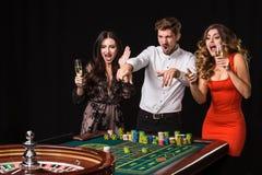 Duas jovens mulheres e homem atrás da tabela da roleta no fundo preto fotos de stock royalty free