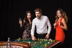Duas jovens mulheres e homem atrás da tabela da roleta no fundo preto imagens de stock royalty free
