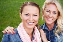 Duas jovens mulheres em um banco em um parque Fotografia de Stock