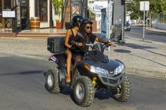 Duas jovens mulheres em um quadrilátero bike em Albuferia Portugal fotografia de stock
