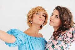 Duas jovens mulheres encantadores bonitas no vestido do verão que faz o selfie na câmera frontal, no fundo branco imagem de stock