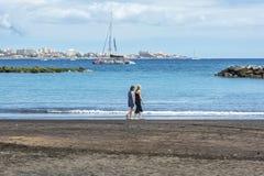 Duas jovens mulheres estão andando na praia perto da água Fotos de Stock Royalty Free