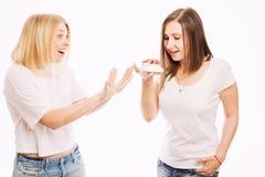 Duas jovens mulheres estão comendo um bolo fotografia de stock