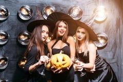 Duas jovens mulheres felizes em trajes pretos do Dia das Bruxas da bruxa no partido Foto de Stock