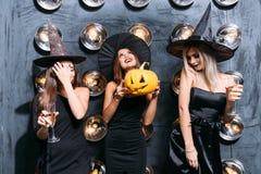Duas jovens mulheres felizes em trajes pretos do Dia das Bruxas da bruxa no partido Fotos de Stock