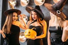 Duas jovens mulheres felizes em trajes pretos do Dia das Bruxas da bruxa no partido Fotografia de Stock Royalty Free