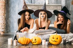 Duas jovens mulheres felizes em trajes pretos do Dia das Bruxas da bruxa no partido Imagem de Stock
