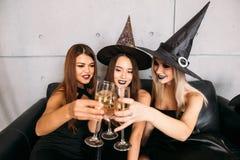 Duas jovens mulheres felizes em trajes pretos do Dia das Bruxas da bruxa no partido Imagem de Stock Royalty Free
