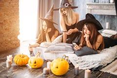 Duas jovens mulheres felizes em trajes pretos do Dia das Bruxas da bruxa no partido Imagens de Stock