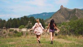 Duas jovens mulheres guardam as mãos e correm-nas ao longo do campo gramíneo verde contra montanhas Georgian magníficas, louro e  filme