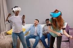 Duas jovens mulheres multirraciais que dan?am vidros vestindo da realidade virtual quando seus noivos que sentam-se no sof? e no  imagens de stock royalty free