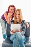 Duas jovens mulheres nas calças de brim que adiam uma tabuleta fotografia de stock royalty free