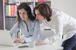 Duas jovens mulheres no escritório que trabalha junto no desktop Fotografia de Stock Royalty Free