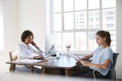 Duas jovens mulheres no trabalho, nos originais do telefone e da leitura imagens de stock