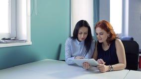 Duas jovens mulheres olham para acolchoar no escritório ou no café filme