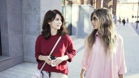 Duas jovens mulheres que andam e que falam em uma rua do verão com copos de café filme