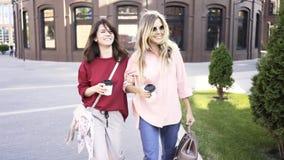 Duas jovens mulheres que andam em uma rua do verão com copos de café vídeos de arquivo