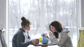 Duas jovens mulheres que bebem o chá em um café filme