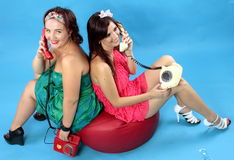 Duas jovens mulheres que chamam telefones no fundo azul Imagem de Stock